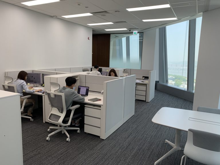 Four people working on computers in the open space office