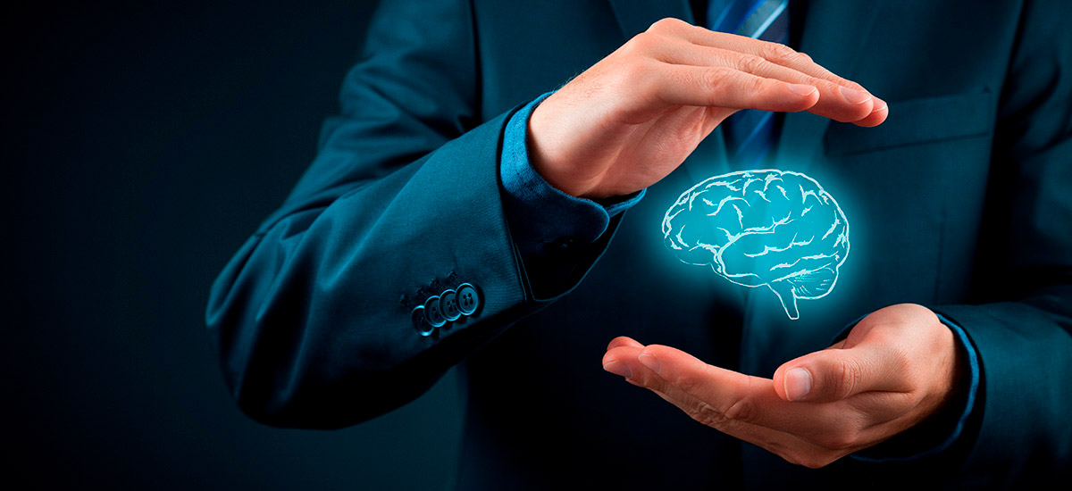 A person in a black suit holds his hands around the icon of a human brain