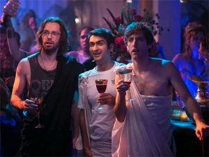 Three guys wearing togas hold wine glasses and look confused