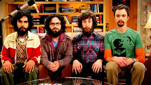 Four students, each wearing a mustache and a beard, are sitting on a sofa, all stiff and overly serious