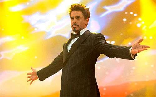 Robert Downey Jr. wearing a suit and a tie stands with his arms spread and looks full of himself