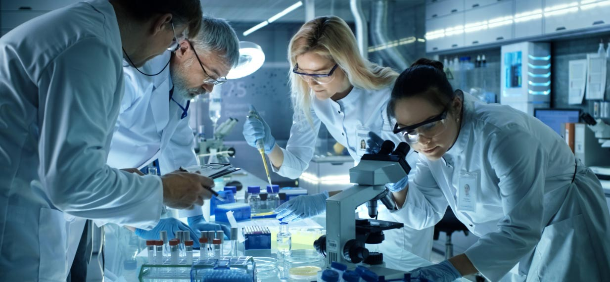 Four middle-aged health workers conduct research at the lab