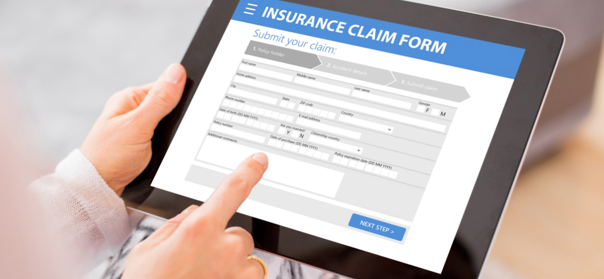 A person is filing an insurance claim form on a tablet
