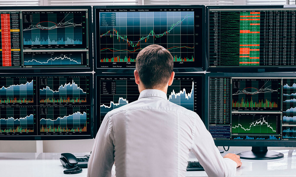 A person is monitoring the activity on stocks market using 6 monitors