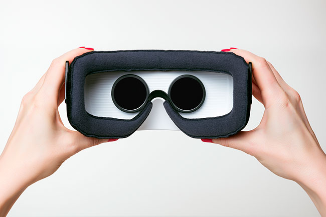 Hands hold VR headset
