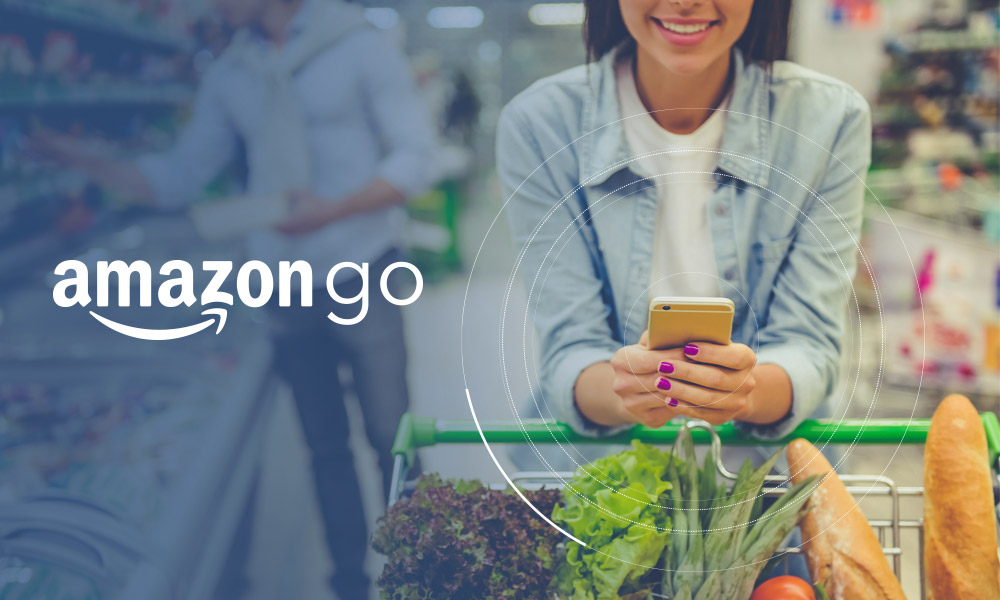 A person pushing a trolley with groceries and using the phone next to Amazon Go logo